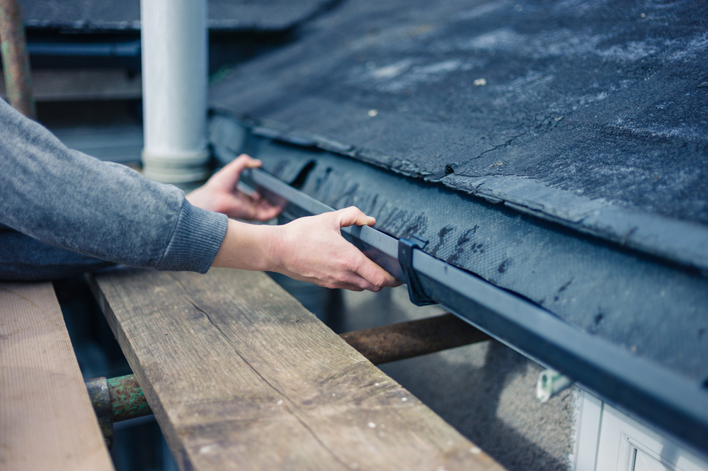 worker repairs gutters on home